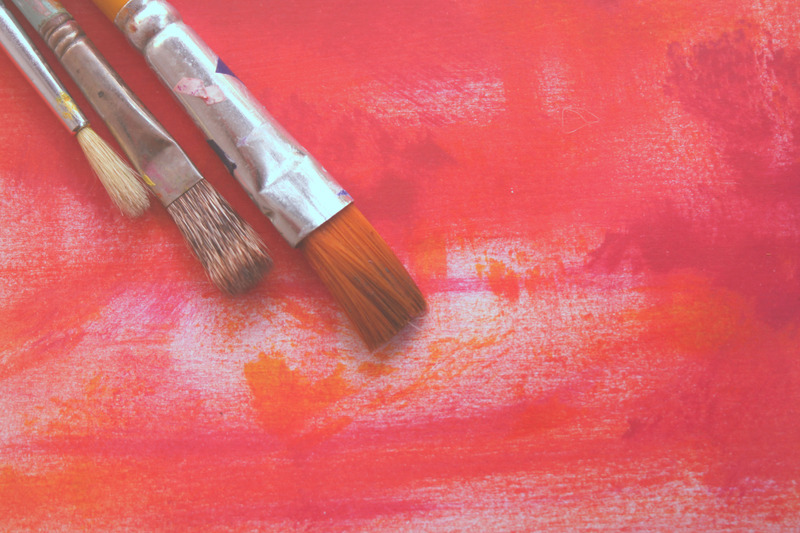 Paint brushes on a canvas painted in red hues.
