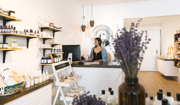 Shop owner behind counter in retail shop selling organic bath and body products